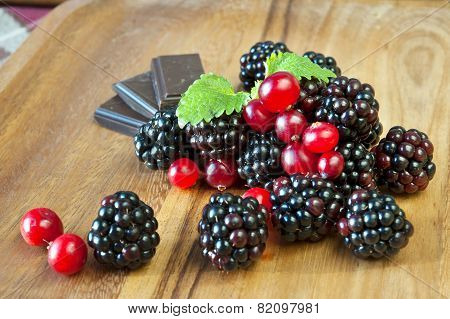 Fresh Blackberries And Cranberries With Chocolate On Wooden Dish.