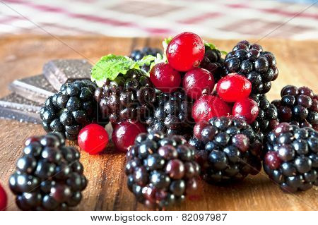 Fresh Cranberries And Blackberries With Mint And Chocolate On Wooden Plate.