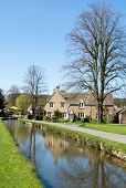 stock photo of slaughter  - Cottages by a small stream in the Cotswold village of Lower Slaughter - JPG