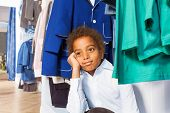picture of clothes hanger  - African boy with hand on his cheek sitting under hangers with clothes after shopping in the clothes store - JPG