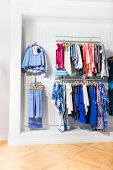 stock photo of clothes hanger  - Many children clothes hanging on hangers in the clothing store on the background of white wall - JPG