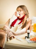 foto of throat  - Portrait of little girl sitting in bed and using throat spray - JPG