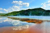 stock photo of steamy  - red steamy surface and reflection of the clouds in Midway Geyser Basin in Yellowstone National Park Wyoming - JPG