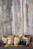 picture of celandine  - Healing herbs in hessian bags on old wooden background herbal medicine - JPG