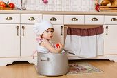 image of chef cap  - Little girl in apron and cap of the cook sitting in the kitchen in the house - JPG