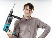 foto of hand drill  - Young man with drilling machine in his hands ready to professional constructing work - JPG
