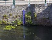 stock photo of water shortage  - water gauge in a old stone canal in amersfoort netherlands - JPG
