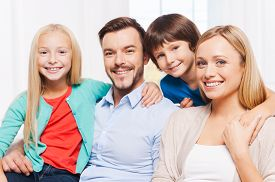 pic of bonding  - Happy family of four bonding to each other and smiling while sitting indoors - JPG