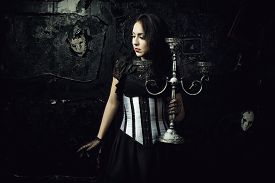 stock photo of gothic girl  - Pretty scared girl in dark room with candlestick over wall with masks - JPG