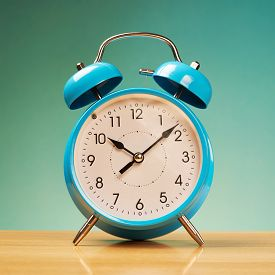 image of blue-bell  - Blue alarm clock on the wooden surface against the blue background - JPG