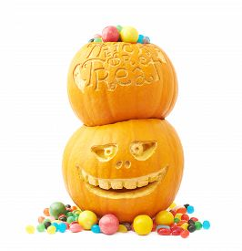 pic of jack-o-laterns-jack-o-latern  - Pile of two Jack o lantern Halloween pumpkins filled with multiple colorful sweets and candies - JPG