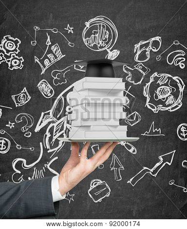 Student's Hand Is Holding A Gadget With Book And Graduation Hat On It. Background With Sketched Ico