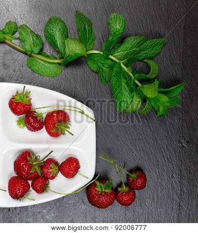 Strawberries Inside Ceramic Plate With Mint Leaves Over Black Slate Background