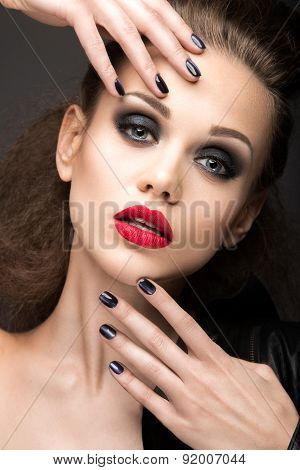Beautiful girl in leather jacket with bright makeup and manicure Cat's Eye. Beauty face. Nail Design