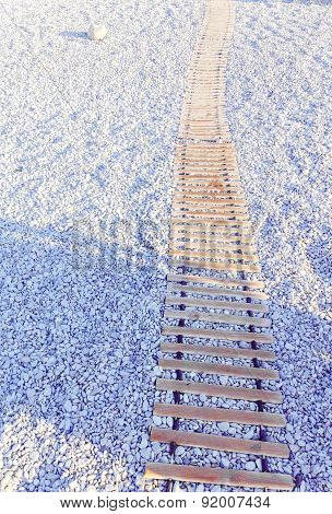 Wooden Walkway On Beach Of Pebbles
