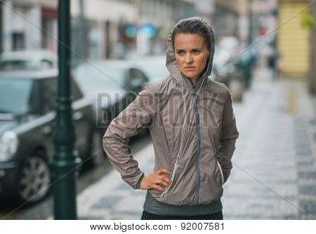 Woman Runner Wearing Rain Gear Stopped And Feeling Unmotivated