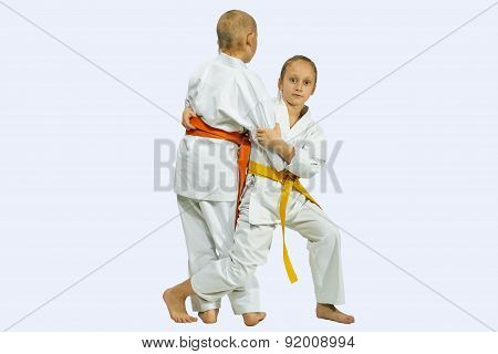 Girl and boy in judogi are training throwing