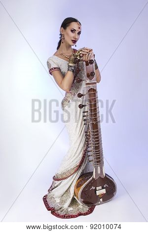 Beautiful Indian Woman In Sari With Oriental Jewelry Posing With Sitar