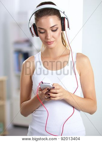 Woman with headphone listening music standing at home.
