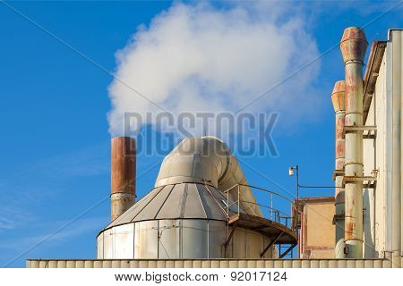 Smoking chimneys of a factory against a blue sky