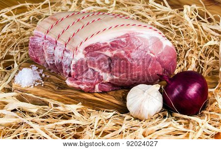 Farm British Boneless Pork Shoulder on cutting board and straw, onion, garlic and Sea salt