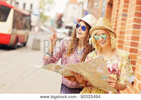 A picture of two girl friends using a map in the city