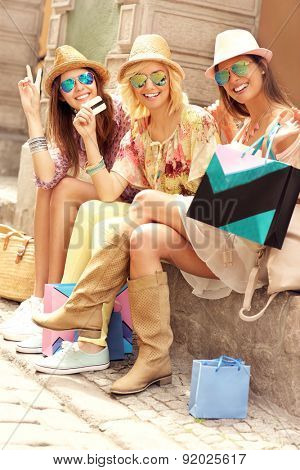 A picture of a group of happy friends resting after shopping in the city