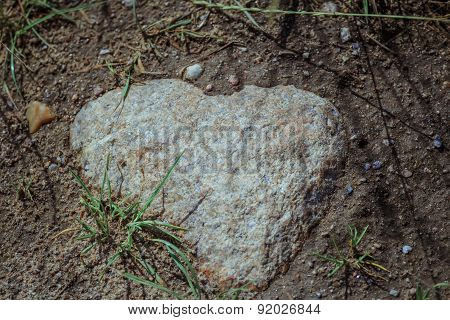 Close-up Of Natural Heart Shaped Granite Stone In Field Soil