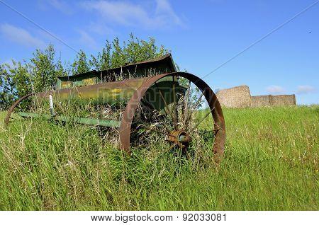 Old rusty grain seeder in a field
