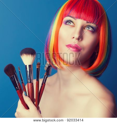 Beautiful Woman Wearing Colorful Wig And Holding Make-up Brushes Against Blue Background