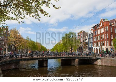 Amsterdam - Panoramic view of Bridge over Amstel river with people and bicycles