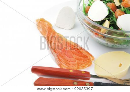 healthy diet food - fresh green lettuce salad with smoked salmon an light white goat feta cheese in transparent bowl isolated over white background