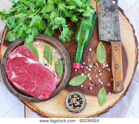 Raw beef steak with salt and peppers on a wooden backgraund