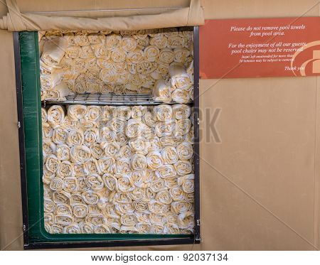 Rolled yellow and white towels stacked on metal rack tall with sign