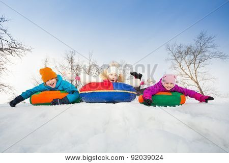 Happy group of children slide on tubes in a row