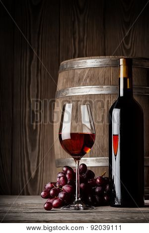 Glass of red wine with bottle and keg standing