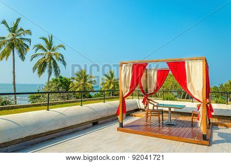 Pergola with tables, chairs and red curtains