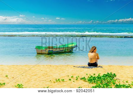 Exotic beach, young girl, fishing boat and water