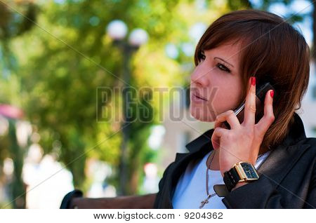 The Young Girl Speaks By Phone In Park