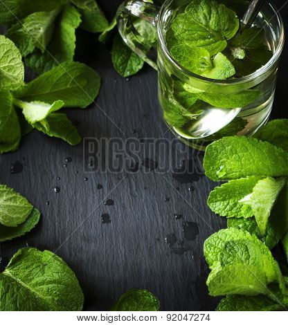 Mint Tea And Mint Leaves Over Black Background With Copy Space.