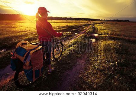 Woman with loaded bicycle on the wet unpaved rural road at sunset