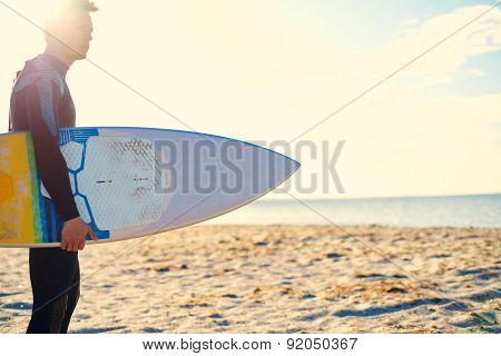 Surfer Carrying His Board Backlit By The Sun