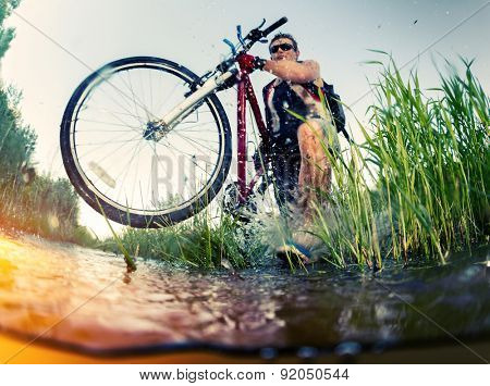 Young man crossing the swamp with bicycle