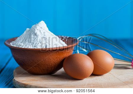 Baking cake in rural kitchen - dough recipe ingredients eggs, bowl with flour and whisk, screen on v