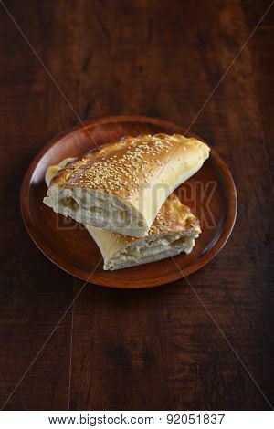 Fatayer - Hot cheese-stuffed arabic pastry bread cut into two pieces.