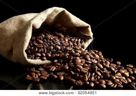 Overturned Bag Full Of Coffee Beans On Black