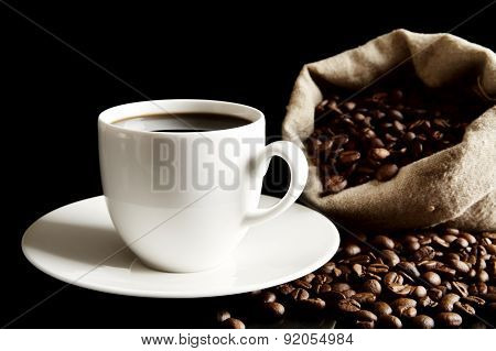 Cup Of Coffee With Saucer With Bag With Coffee Beans On Black