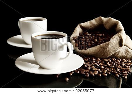 Cups Of Coffee With Saucer With Bag With Coffee Beans On Black
