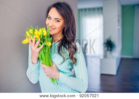 Beautiful casual woman with a tulip bouquet in front of a grey wall