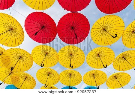 Many open in sky umbrellas  give a guarantee that rain will not spoil the day. Red, yellow and blue